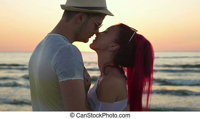 Young beautiful couple kissing at sunrise on the beach
