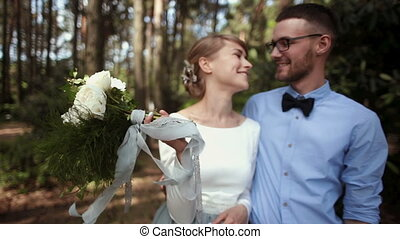 Young beautiful couple newlyweds kiss against a background of green tree in the park