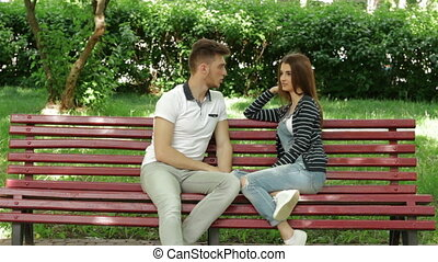 young beautiful couple on a bench in the Park talking