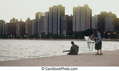 Young Beautiful couple on the shore of Michigan lake, Chicago, America. Woman draw, man play guitar.
