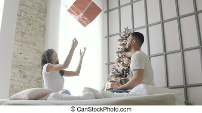 young beautiful couple posing gifts sitting on the bed. Christmas tree on the background.