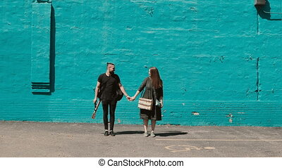 Young beautiful couple posing near the bright blue wall....