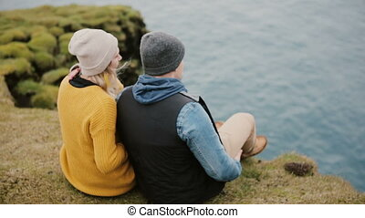 Young beautiful couple sitting at the edge of the cliff and enjoying the beautiful view. Photographer taking photos.