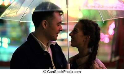 Young beautiful couple spending time together on date in amusement park at night. Rainy weather, autumn. Lovers standing under umbrella. Illuminated background.