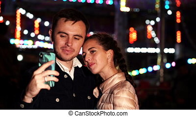 Young beautiful couple spending time together on date, taking selfie portrait with smartphone in amusement park at night. Illuminated background. Millennial lifestyle.