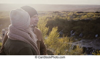 Young beautiful couple standing in sunny valley and talking, enjoying the beautiful view in Iceland.