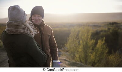Young beautiful couple standing on the bridge and talking, have a rest. Man and woman traveling, hair waving on wind.