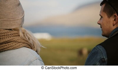 Young beautiful couple standing on the field and talking....