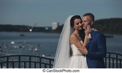 Young beautiful couple standing on the quay of river and hugging in their wedding day. Newlyweds spending time together.