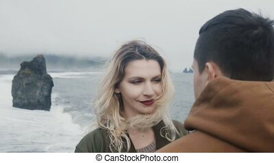 Young beautiful couple standing on the shore of the sea and...