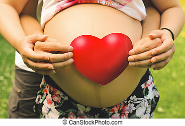 Young beautiful couple take their hands together with red heart on the belly of a pregnant woman close-up in the summer season