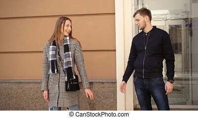 Young beautiful couple tenderly holding hands and smiling while posing on camera.