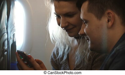 Young beautiful couple traveling by plane together. Happy...