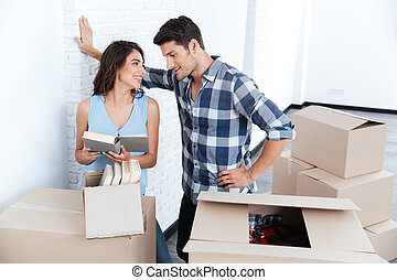 Young beautiful couple unpacking in new flat