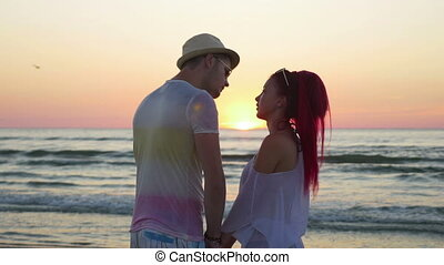 Young beautiful couple watching an amazing sunset and kissing on beach