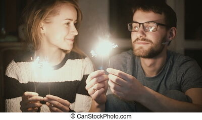 Young beautiful couple with sparkler sitting in the evening at home. Man and woman spending time together, kissing.