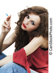 Young beautiful curly long-haired brunette woman with cigarette isolated on white background