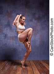 Young beautiful dancer in beige swimwear dancing on lilac...