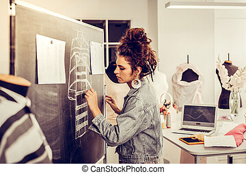 Young beautiful designer drawing a sketch on a blackboard.