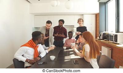 Young beautiful employees enjoying coffee during break.