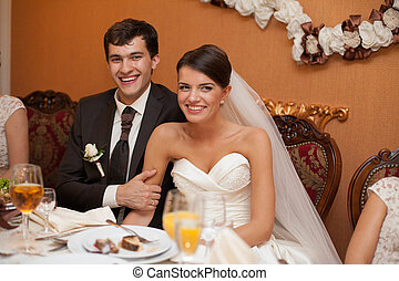 young beautiful extravagant wedding couple at the table