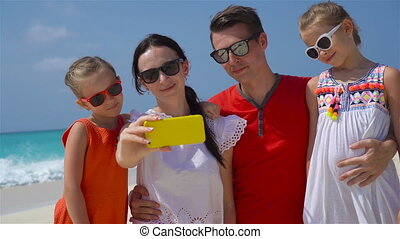 Young beautiful family taking selfie portrait on the beach