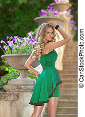 Young beautiful fashionable girl model in fashion green dress posing on stairs over blossom park background.