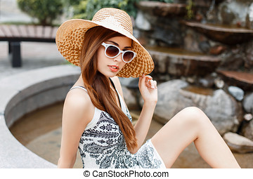 Young beautiful fashionable stylish girl in sunglasses and hat resting on a summer day.