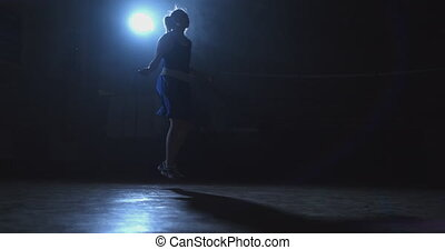 Young beautiful female boxer training in the gym skipping rope the movement of the camera slide.
