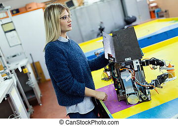 Young beautiful female engineer testing robot in workshop