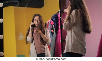Young beautiful female is talking on cell phone standing in front of mirror.