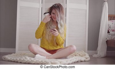 Young beautiful female sits on the floor in her bedroom, drink a coffee and using a smartphone. The wind blows the hair.