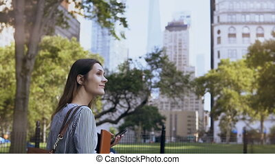 Young beautiful female walking through the park at work. Businesswoman holding the documents and using smartphone.