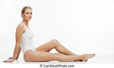 Young, beautiful, fit and natural blond woman in white ...