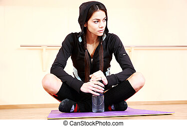 Young beautiful fit woman sitting on the yoga mat at gym