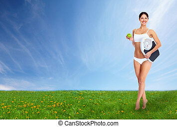 Young beautiful fitness woman. On blue sky background.
