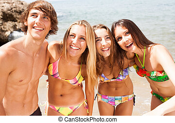 young beautiful friends group laughing on the beach