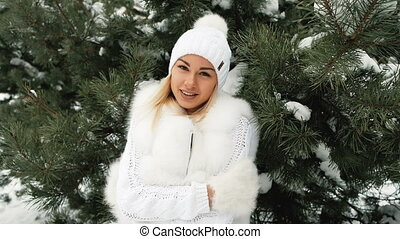 Young beautiful frozen blonde hug herself in forest.