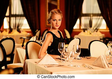 Young beautiful girl alone in a luxury restaurant