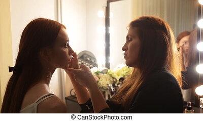 Young beautiful girl applying make-up