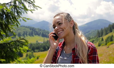 Young beautiful girl calls by mobile phone in the mountains