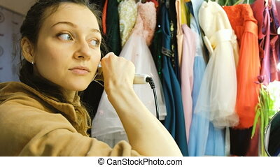 Young beautiful girl curls her hair on a curling robe in the dressing room