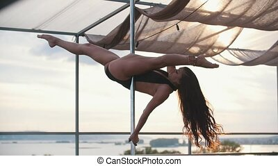 Young beautiful girl dancer with flowing hair dancing outdoor - pole dance, slow-motion
