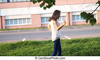young beautiful girl dancing in a park. woman in jeans dancing in the street