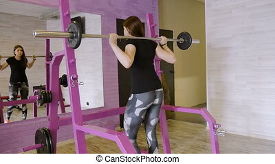 Young beautiful girl doing exercises with dumbbells at the gym.