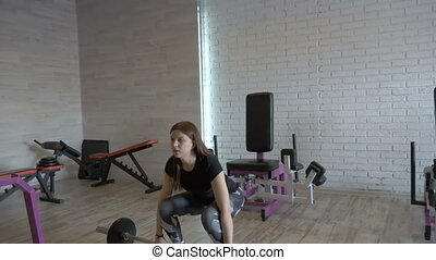 Young beautiful girl doing exercises with dumbbells at the gym. slow motion