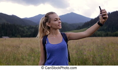 Young beautiful girl doing selfie in the mountains