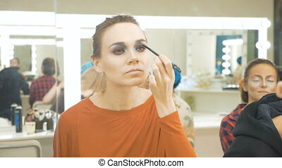 Young beautiful girl draws shadows on the eyelids. She is standing in front of the mirror and doing makeup. In a beauty salon