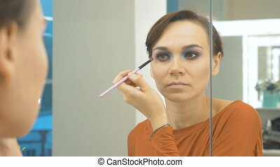 Young beautiful girl draws shadows on the eyelids. She is standing in front of the mirror and doing makeup.