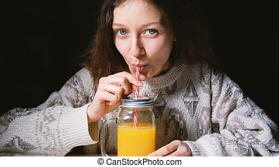 Young beautiful girl drinking fresh orange juice in a glass bottle with a straw